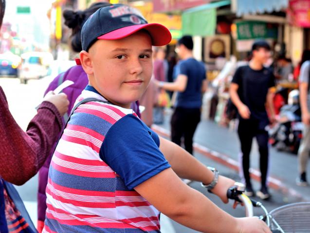 Мальчик на велосипеде на городской улице